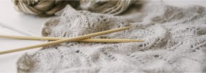 knitting needles on a light gray knitted piece